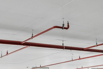 Fire sprinkler and red pipe on white ceiling background