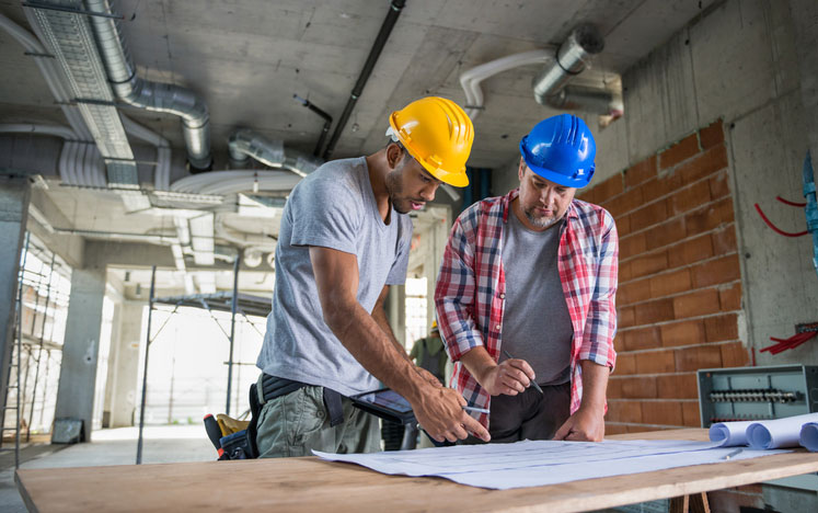 Two Construction Workers Looking Blueprint Together
